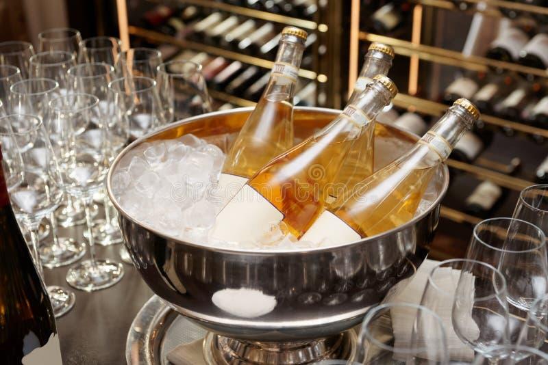 Flessen oranje wijn in kom met ijs stock fotografie