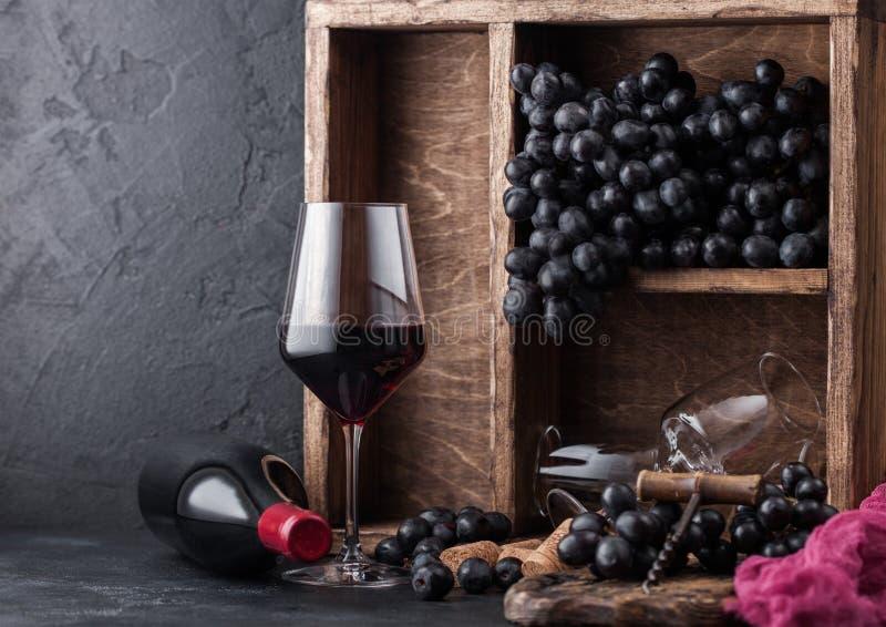 Flessen rode wijn met donkere druiven binnen uitstekende houten doos op zwarte steenachtergrond Het elegante wijnglas met kurkt e stock foto's