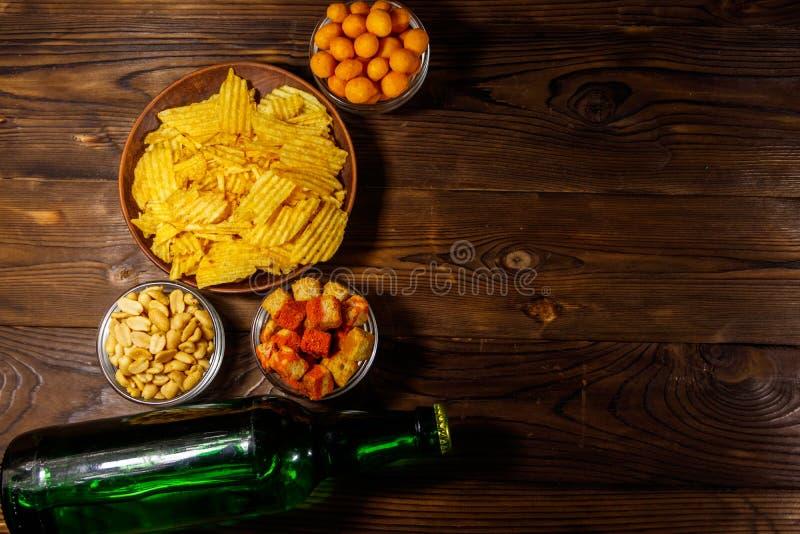 Flessen van bier en diverse snacks voor bier op houten lijst stock foto