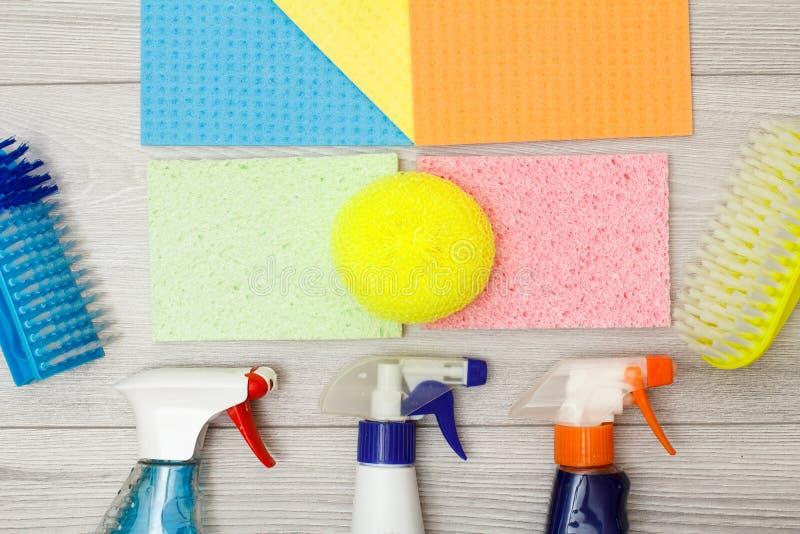 Flessen van detergens, kleuren microfiber servetten, synthetische spons en borstels voor het schoonmaken royalty-vrije stock afbeelding