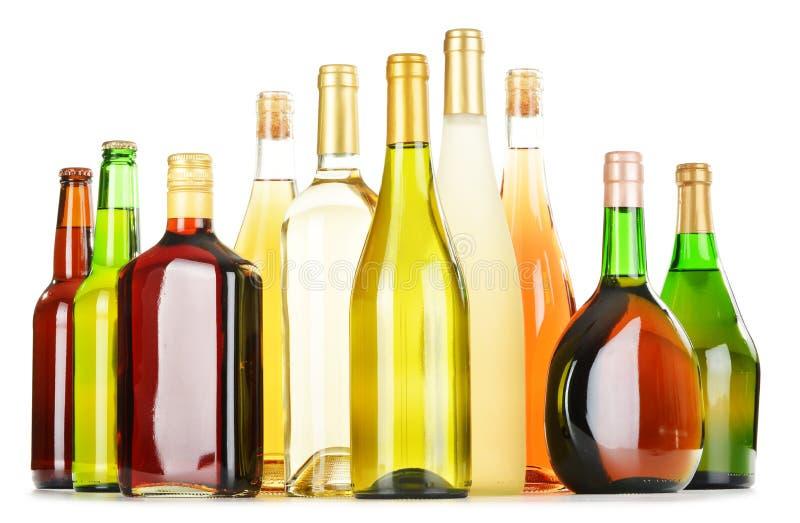 Flessen van geassorteerde alcoholische dranken op wit stock afbeelding
