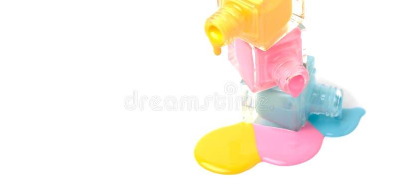 Flessen van het trio de kleurrijke nagellak op gemorste verf stock foto