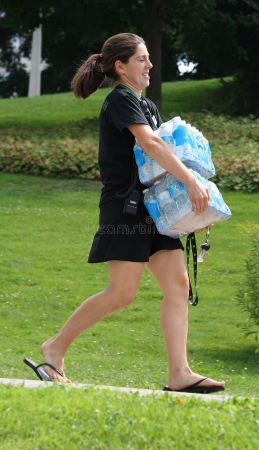 Flessen van het Water van de vrouw de Dragende stock fotografie