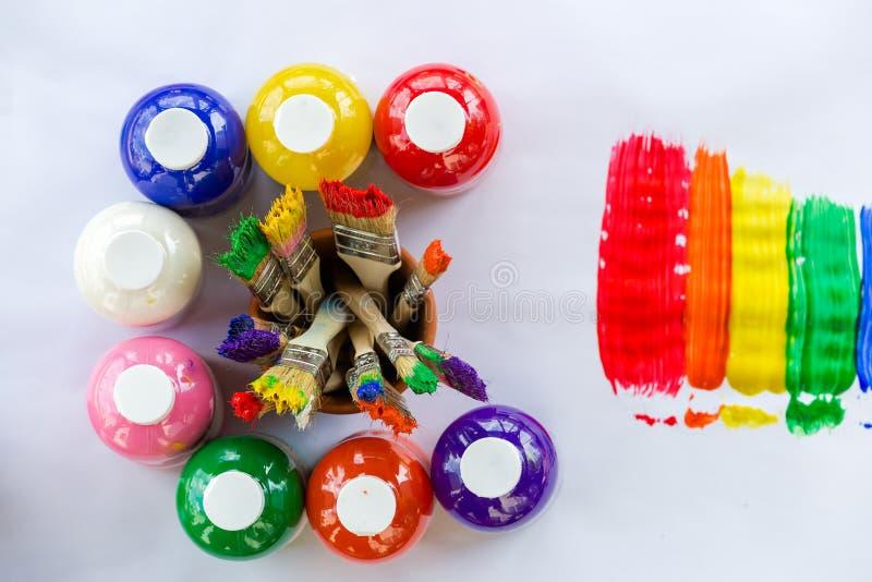 Flessen van kleurrijke verf met verfborstels stock afbeeldingen