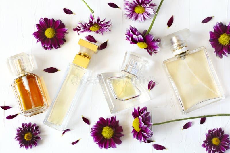 Flessen van parfum en bloemen op witte achtergrond stock afbeelding