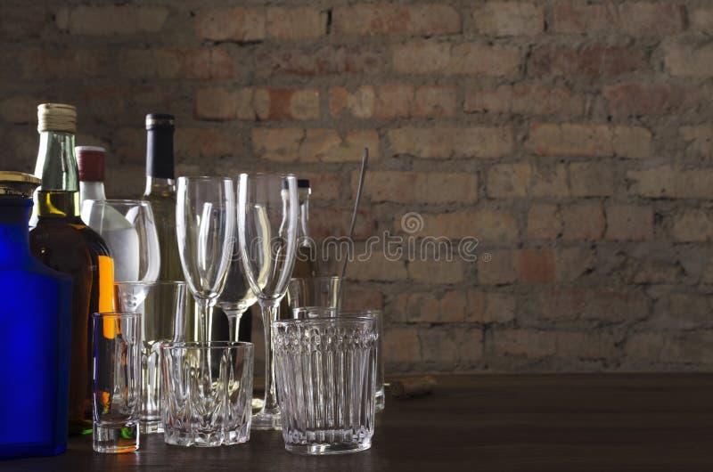 Flessen van whisky, wijn en andere alcoholische dranken, andere glazen voor dranken op tafel tegen de oude baksteenwand Avond op  stock foto's