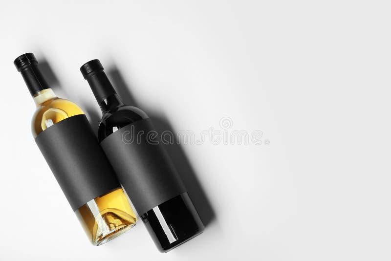 Flessen wijn met lege etiketten op lichte achtergrond stock afbeelding