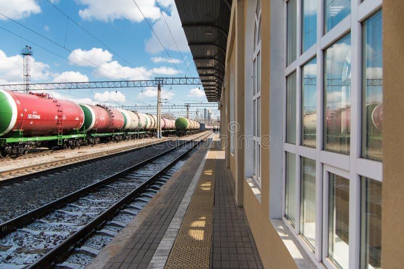 Flete el tren con los tanques se coloca en los carriles al lado del edificio de la estaci?n central Los tanques del tren con petr fotografía de archivo libre de regalías