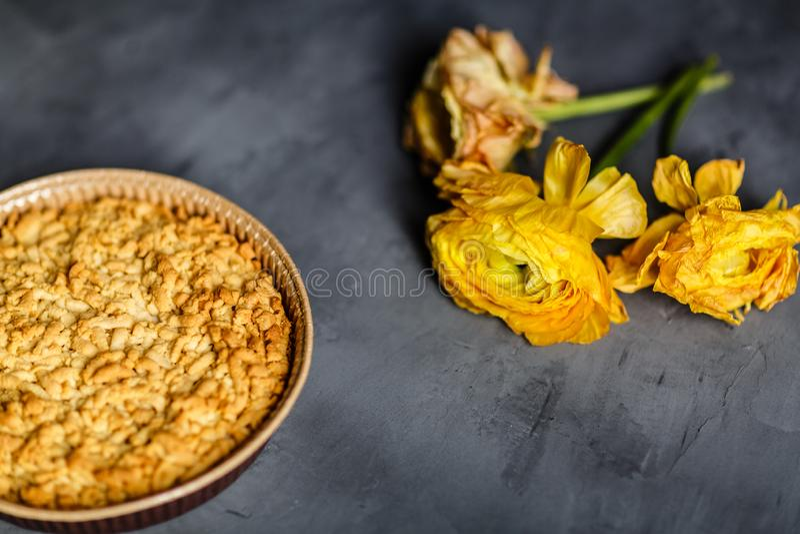 Fleur, biscuits jaunes et tarte aux pommes se trouvant sur le fond gris image stock