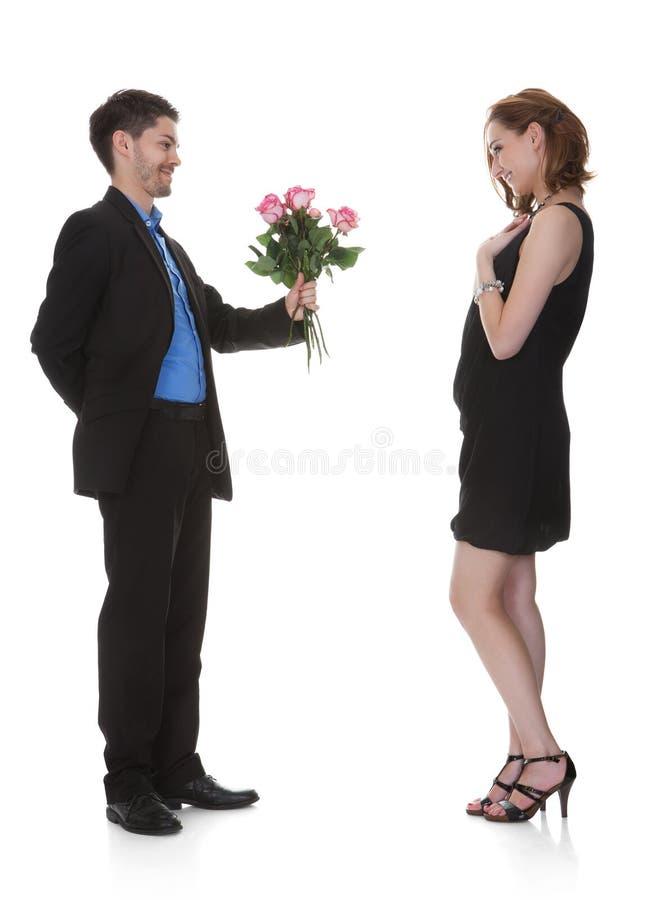Fleur d'offre d'homme à la belle femme photographie stock