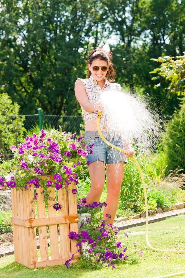 Fleur de arrosage de sourire de boyau de femme de jardin d'été photos libres de droits