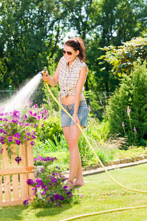 Fleur de arrosage de sourire de boyau de femme de jardin d'été photographie stock