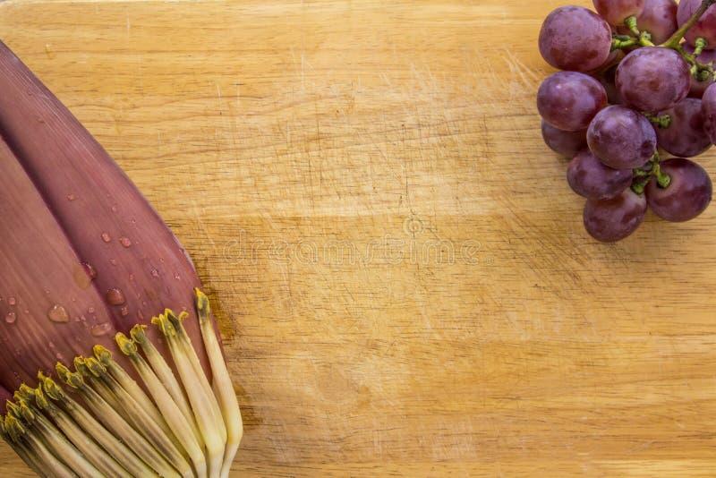 Fleur de banane avec l'eau et le raisin rouge sur le fond en bois photographie stock libre de droits
