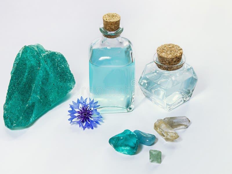 Fleur de bleuet et eau bleue ou pétrole d'aromatherapy dans la bouteille en verre Cristaux minéraux naturels sur le fond blanc photo libre de droits