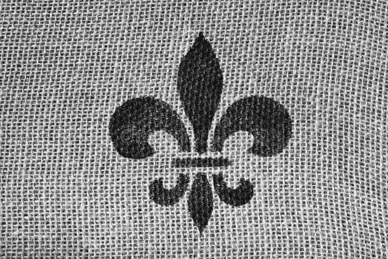 Fleur de Lis. A Black and White Fleur de Lis on Burlap stock image