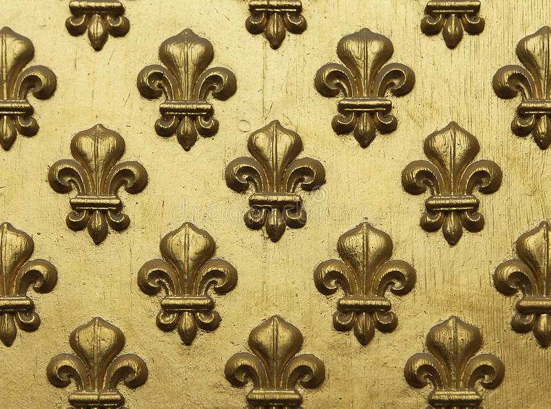 Fleur de Lis Pattern In Gold. Fleur-de-lis painted in gold in a repeating pattern on a grand entrance to a Paris building. This decorative element represents royalty free stock photos