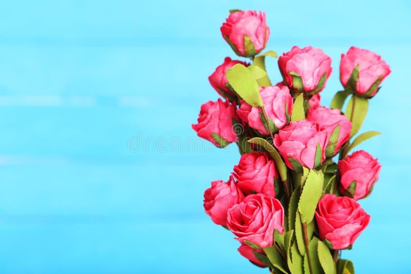 Fleur de Rose sur le vase, sur le fond bleu photographie stock