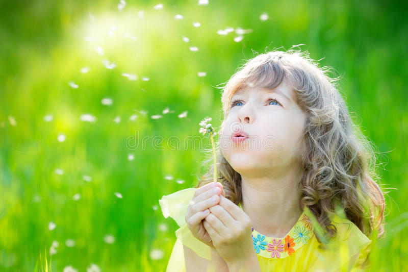 Fleur de soufflement de pissenlit d'enfant heureux dehors photographie stock