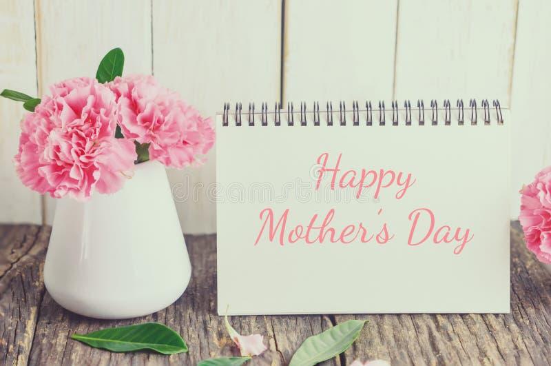 Fleur rose d'oeillet avec le texte heureux de jour du ` s de mère sur la carte blanche image libre de droits