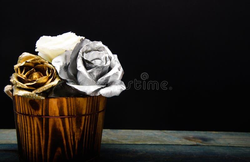 Fleur rose fraîche d'argent et d'or dans le vase en bois Beaut? grunge Luxe et succ?s décor antique métallisé richesse images stock