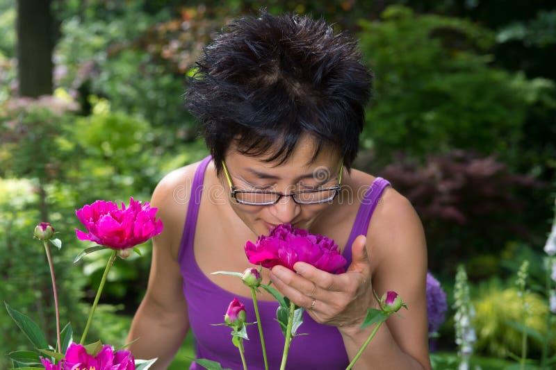 Fleur sentante de femme asiatique photographie stock