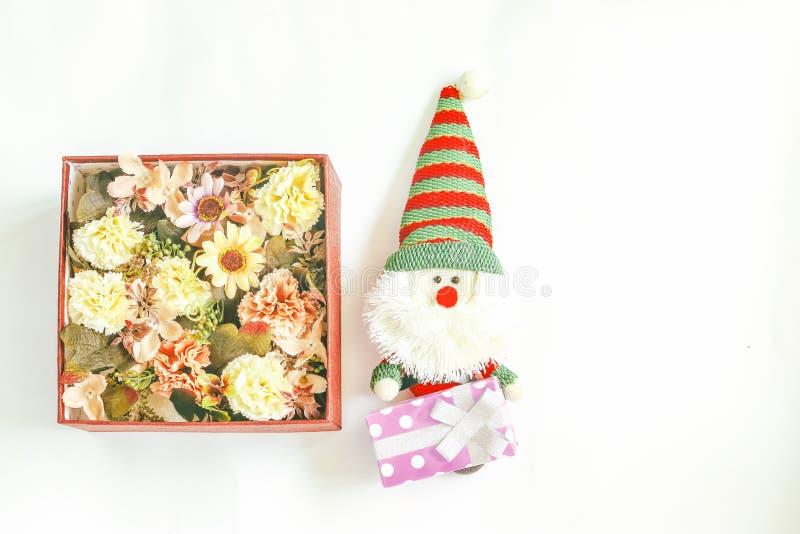 Fleurissez dans la boîte du présent et de la poupée de Santa photos stock