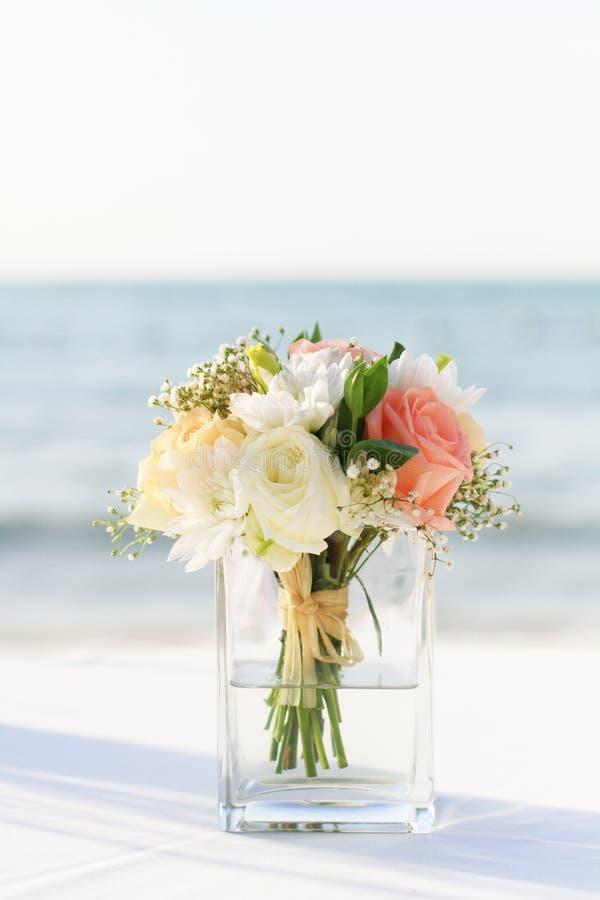 Fleurissez dans le mariage de vase sur la plage image stock