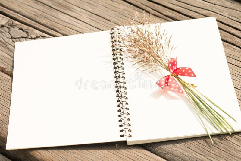Fleurissez l'herbe avec l'arc rouge et le carnet sur la table en bois image stock