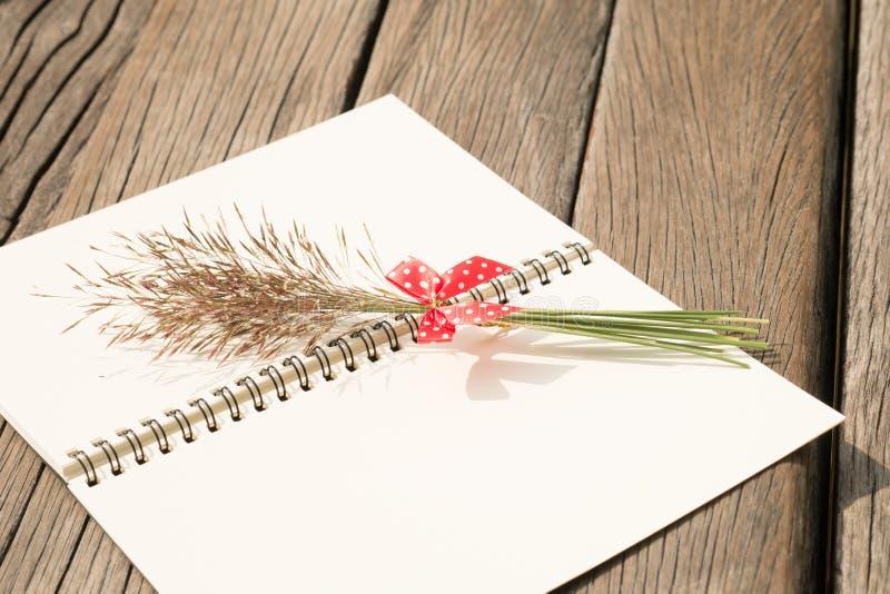 Fleurissez l'herbe avec l'arc rouge et le carnet sur la table en bois images libres de droits