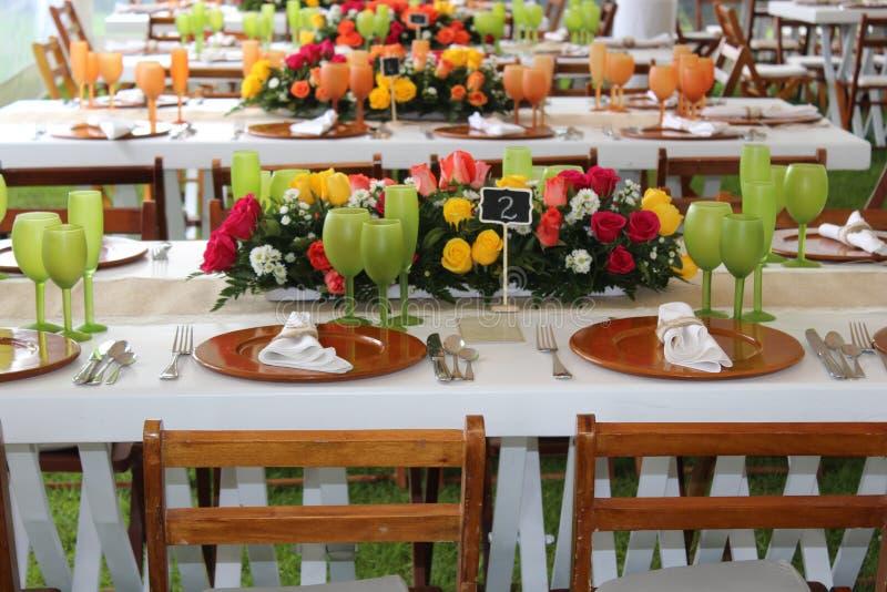 Fleurissez le bouquet avec des roses épousant la table avec les verres verts images libres de droits
