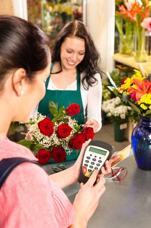 Fleuriste de femme vendant le propriétaire de fleurs payant la carte photos libres de droits