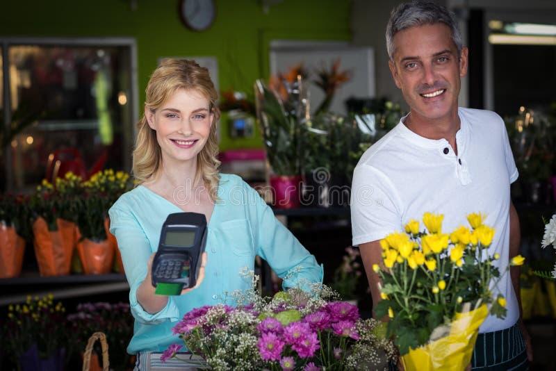 Fleuriste de sourire montrant le terminal de carte de crédit dans le fleuriste photographie stock libre de droits