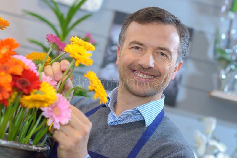 Fleuriste masculin arrangeant des fleurs image libre de droits