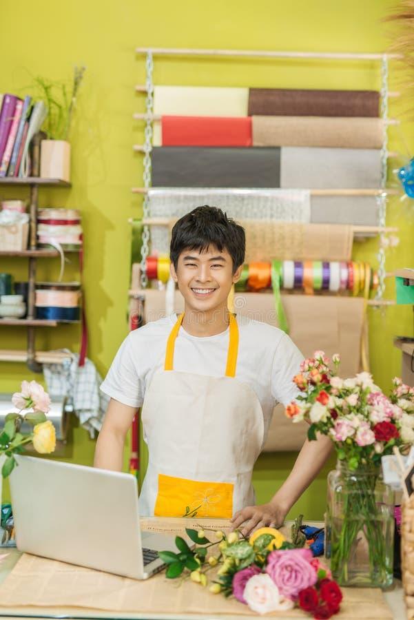 Fleuriste masculin asiatique heureux à l'aide de l'ordinateur portable au compteur dans le fleuriste images stock