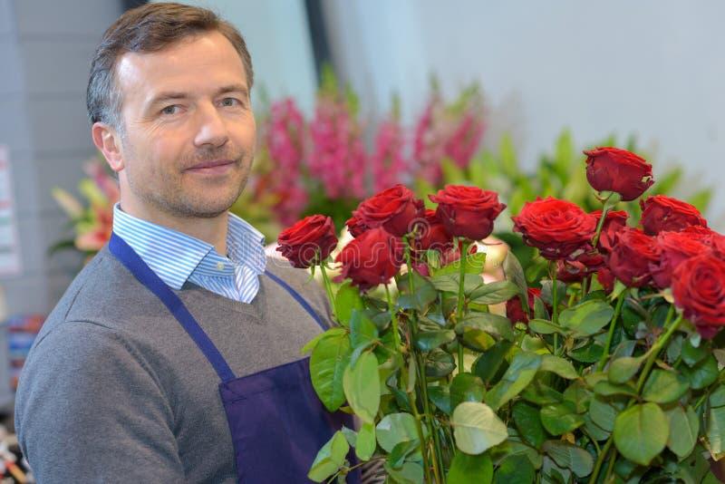 Fleuriste masculin tenant les roses rouges de bouquet photographie stock