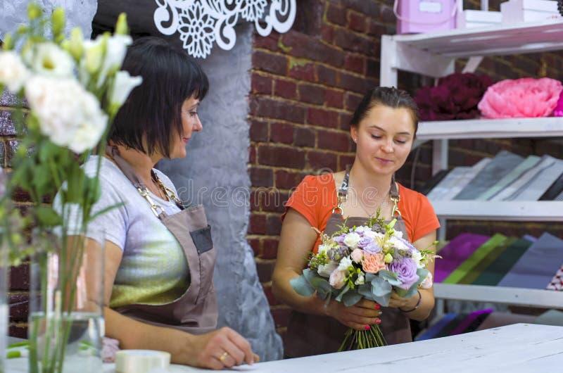 Fleuristes professionnels s'chargeant du bouquet de mariage de fleur dans le studio de conception florale image stock