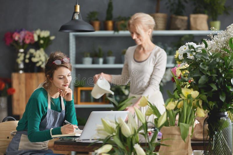 Fleuristes travaillant dans le fleuriste photo libre de droits