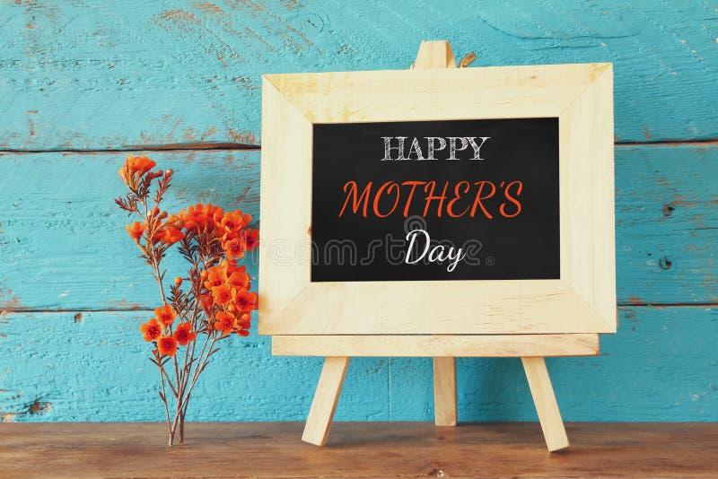 Fleurs à côté de tableau noir avec l'expression : JOUR de MÈRES HEUREUX, sur la table en bois Concept heureux du jour de mère photographie stock