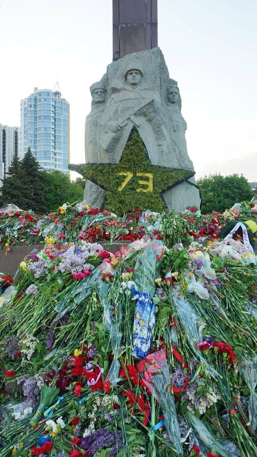 Fleurs apportées par des personnes au monument de la gloire sur Victory Day au-dessus du fascisme, le 9 mai photo libre de droits