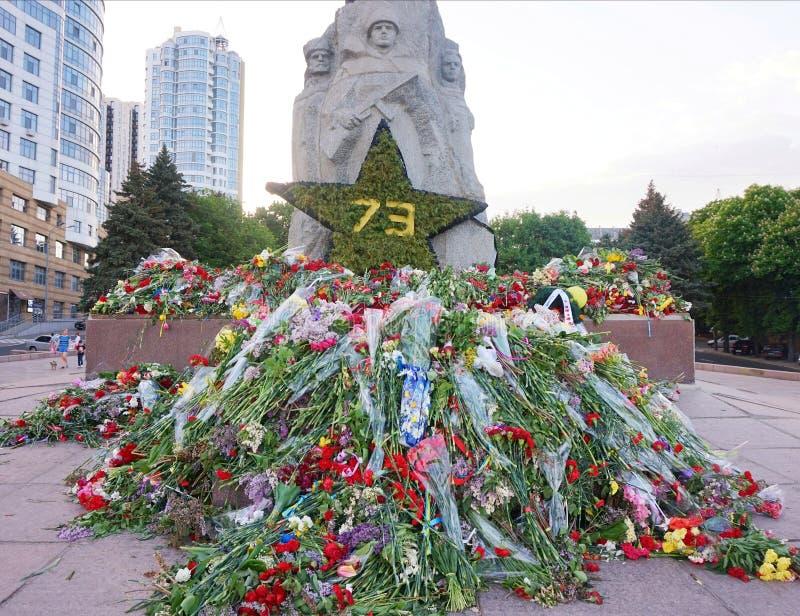 Fleurs apportées par des personnes au monument de la gloire sur Victory Day au-dessus du fascisme, le 9 mai photographie stock libre de droits