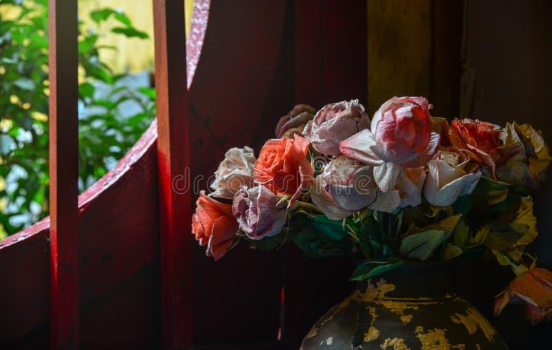 Fleurs artificielles avec la fenêtre en bois photo stock