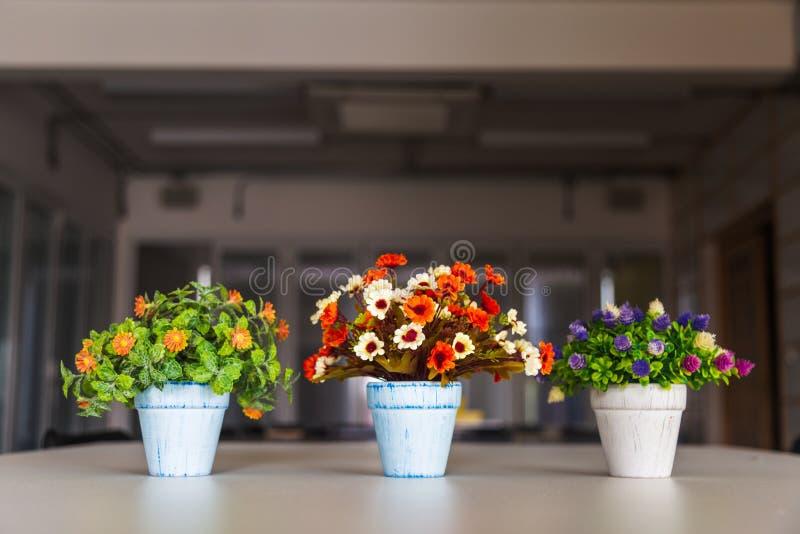 Fleurs artificielles color?es dans le vase sur la table avec le fond de vitrail images stock