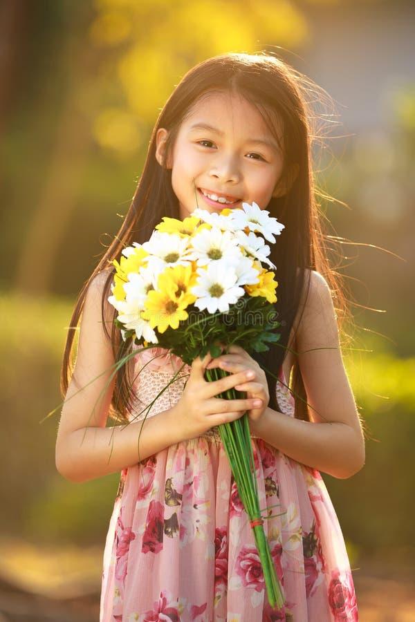 Fleurs asiatiques de sourire de prise de fille photos libres de droits