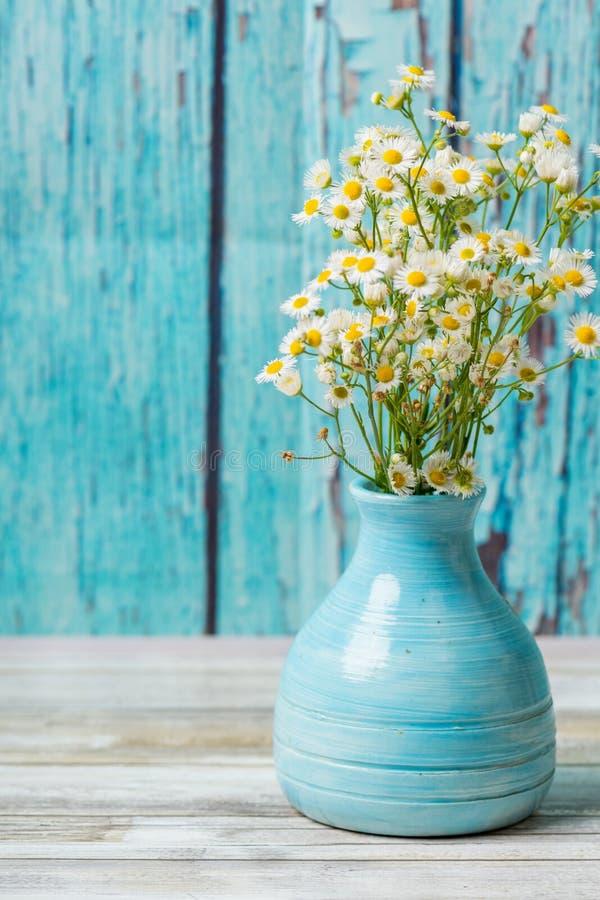 Fleurs blanches dans un vieux vase bleu images stock