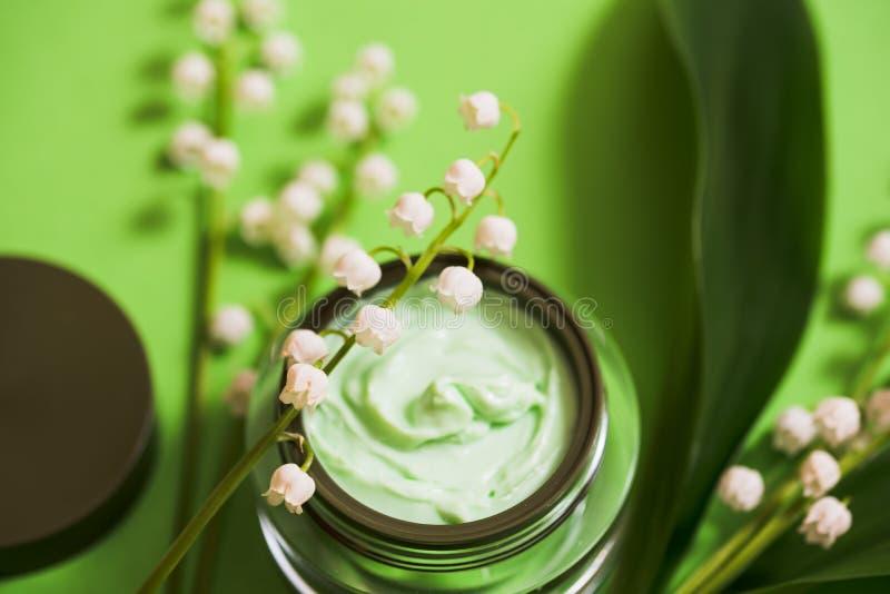 fleurs cosmétiques de crème et du muguet sur un fond vert images stock