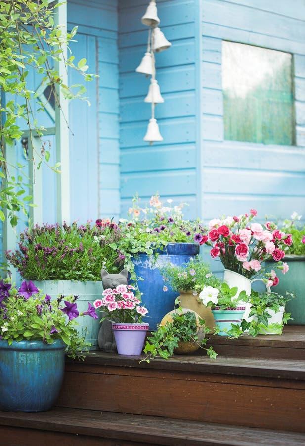 Fleurs d'été et cloche mises en pot de jardin photos stock