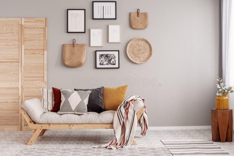 Fleurs dans le vase jaune sur le tabouret en bois dans l'intérieur scandinave beige de salon image stock