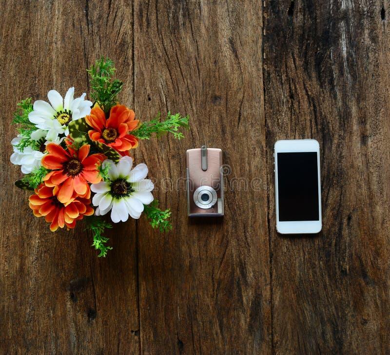 Fleurs dans le vase, l'appareil-photo et le téléphone sur la vieille table en bois images libres de droits