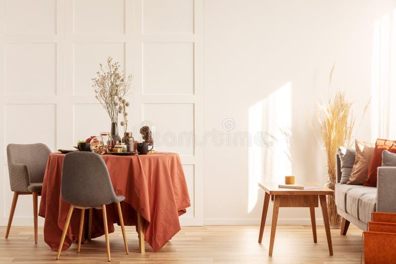 Fleurs dans le vase sur la table de salle à manger couverte de nappe orange-foncé image libre de droits