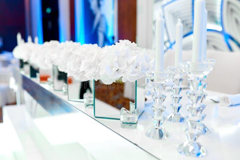Fleurs dans un vase à miroir à côté de petites et grandes bougies sur une table image stock